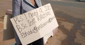 (Photo) Abuja lady display unemployment placard on the street