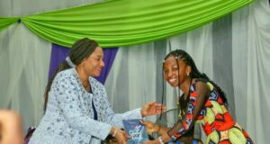 16-year-old author Queen Maadiah Johnson presents her book to Martha Udom Emmanuel, wife of Akwa Ibom governor